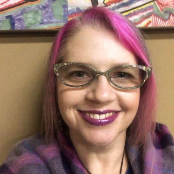 Pink haired woman wearing cat-eye glasses, purple lipstick, and a pink and purple wrap confidently smiles