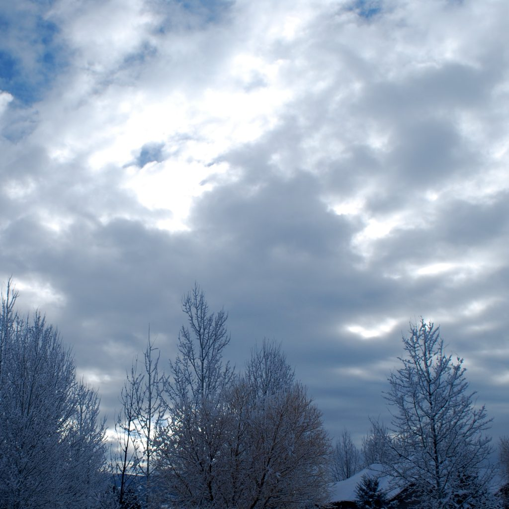 The sun breaks free of heavy cloud cover on a snowy day.