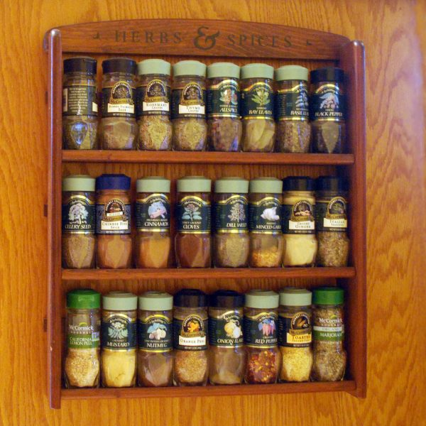 Bottles of spices lined up on a wooden spice rack