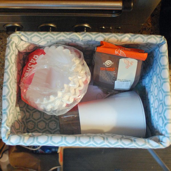 Interior of fabric-lined basket contains coffee filters, a bag of coffee, and a coffee grinder